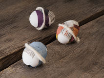 Beautiful selfmade easter eggs. Three selfmade easter eggs taped with newspaper on a wooden table Stock Photo