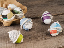 Beautiful selfmade easter eggs. Selfmade trendy easter eggs sticked with newspaper on a wooden table Royalty Free Stock Photos