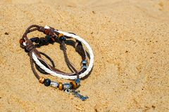 Beautiful semi-precious stone beads. Leather braided bands in the bracelet. Brown and white. On sea sand stock photography