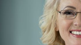Beautiful senior blonde with eyeglasses smiling into camera, health care. Stock footage stock video