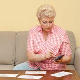 Beautiful senior calculating her debts Stock Photos