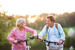 Beautiful senior couple with bicycles outside in spring nature. stock photos