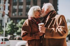 Beautiful senior couple with hot drinks expressing their love on the street. Side view portrait of stylish bearded gentleman kissing nose of his happy wife. He royalty free stock image