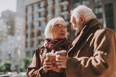 Beautiful senior couple with hot drinks looking at each other and smiling stock photos