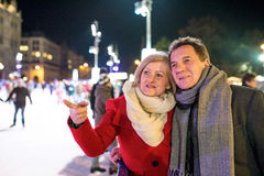 Beautiful senior couple ice skating in city centre. Winter Stock Images
