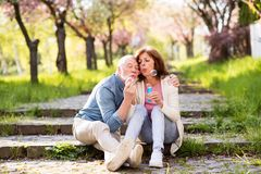 Beautiful senior couple in love outside in spring nature. Beautiful senior couple in love outside in spring nature, sitting on stairs, blowing bubbles with stock photography