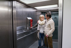 Beautiful senior couple with luggage standing in modern elevator Stock Photography