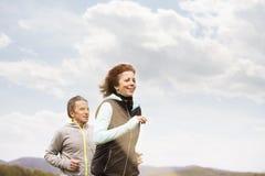 Beautiful senior couple running outside on green hills. Beautiful active senior couple running outside on green hills Stock Photos