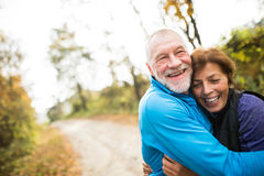 Beautiful senior couple running outside in sunny autumn forest Royalty Free Stock Photos
