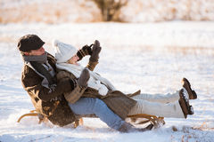 Beautiful senior couple on sledge having fun, winter day. Stock Photo