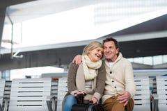 Beautiful senior couple waiting on train station, hugging Stock Photos