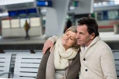 Beautiful senior couple waiting on train station, hugging Stock Image