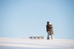 Beautiful senior couple on a walk pulling sledge, winter day. Stock Image