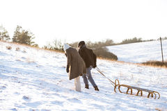 Beautiful senior couple on a walk pulling sledge, winter day. Stock Photo