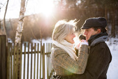 Beautiful senior couple on a walk on sunny winter day. Beautiful senior women and men on a walk in sunny winter nature, hugging Royalty Free Stock Images