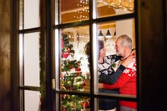 Senior couple at Christmas time. Beautiful senior couple in woolen sweaters with nordinc pattern at Christmas time. Shot through glass Stock Photo