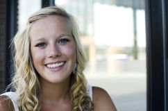 A blonde woman at a coffee shop. A female senior portrait shoot smiles at the camera during a summer shoot in Iowa Royalty Free Stock Photos