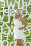 A female senior with white letters in Des Moines. A female senior portrait shoot smiles at the camera during a summer shoot in Iowa Stock Images