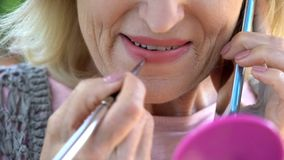 Beautiful senior lady painting her lips, arranging meeting by phone, femininity. Stock photo royalty free stock images