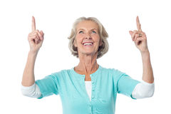 Beautiful senior lady pointing upwards stock photography