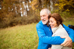 Beautiful senior runners hugging outside in sunny autumn forest Stock Photo