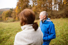 Beautiful senior runners resting outside in sunny autumn nature Royalty Free Stock Photo