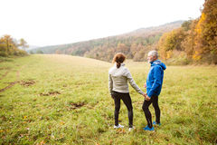 Beautiful senior runners resting outside in sunny autumn nature Stock Photo