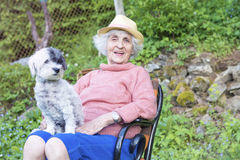 Beautiful Senior smiling woman with straw hat hugging her dog in the mountain Stock Photo