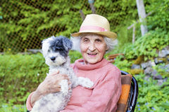 Beautiful Senior smiling woman with straw hat hugging her dog in the mountain Stock Image