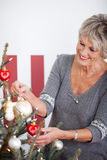 Beautiful senior woman decorating a tree Stock Photo