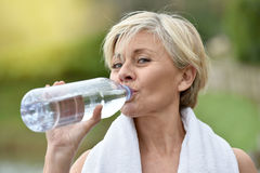 Beautiful senior woman drinking water after excercising Stock Photography