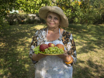 Beautiful senior woman in the garden with apples a. Nd grapes in the plate Royalty Free Stock Photography