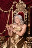 Senior woman sitting in vintage chair. Beautiful senior woman in golden dress with crown sitting in vintage chair Royalty Free Stock Image
