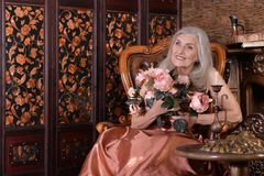 Portrait of beautiful senior woman in golden dress stock photos