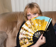 Beautiful senior woman with  hand fan. Royalty Free Stock Image