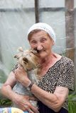 A beautiful senior woman with her dog in a summer garden royalty free stock images