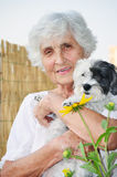 Beautiful senior  woman hugging her dog Stock Photo