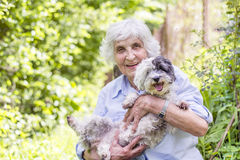 Beautiful senior  woman hugging her dog Royalty Free Stock Image