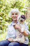Beautiful senior  woman hugging her dog Stock Photo