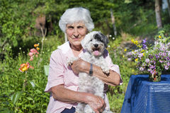 Beautiful senior woman hugging her white dog in the mountain Royalty Free Stock Photography