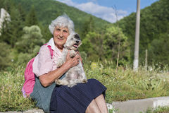 Beautiful senior woman hugging her white dog in the mountain Stock Image