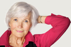 Beautiful senior woman portrait. Senior woman portrait  with white hair and  red blouse, holding left arm on the side with hand in the hair Stock Image