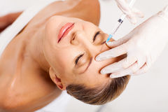 Senior woman injection. Beautiful senior woman receiving cosmetic injection on her forehead Stock Images