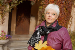Beautiful  senior woman relaxing in the fall park Stock Images