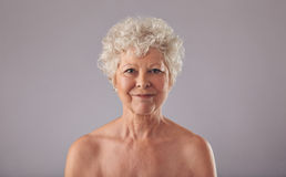 Beautiful senior woman shirtless against grey background Royalty Free Stock Photo