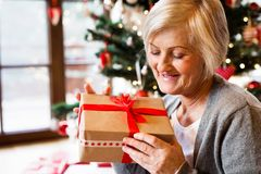 Beautiful senior woman in front of Christmas tree with present. Beautiful senior woman sitting on the floor in front of illuminated Christmas tree inside in her Stock Image