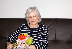 Beautiful senior woman. Beautiful senior woman sitting and holding flowers stock photography