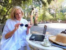 Beautiful senior woman using tablet computer outdoors stock image