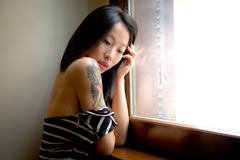 Beautiful sensual asian woman posing thoughtful at window Royalty Free Stock Photos