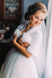 Beautiful sensual blonde bride in robe and white veil posing near window with wedding dress indoors Royalty Free Stock Images